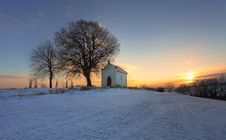 Sunset On Frozen Field With A Chapel Stock Images