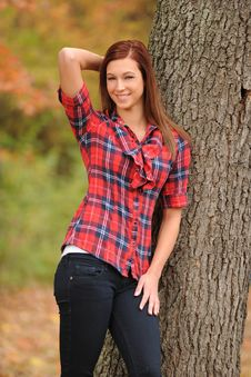 Young Woman Standing By A Tree Stock Images