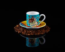 Colourful Coffee Cup And Saucer  On Roasted  Beans Royalty Free Stock Photography