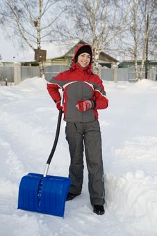 The Girl In A Winter Sports Jacket Holds A Shovel Royalty Free Stock Photo