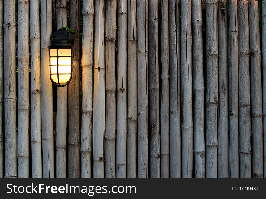Yellow lamp on the bamboo fence