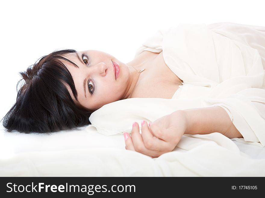 A beautiful young woman is laying on white sheet