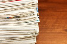 Heap Of Newspapers On A Wooden Table Stock Images