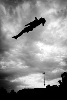 Silhouette Of Gymnast On Trampoline In Sky Stock Photography
