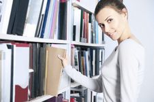 Free Young Women Stands Near Bookshelf Royalty Free Stock Photography - 17782447