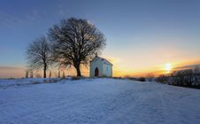 Sunset On Frozen Field With A Chapel Stock Photography