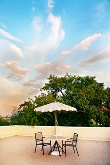 Table, Chairs And Umbrella For Rooftop Relaxation Royalty Free Stock Photography