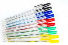 Colored Ballpoint Pens On A Blank Notebook Royalty Free Stock Images