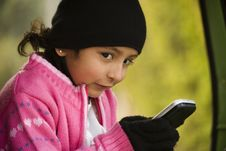 Little Girl Messaging On The Cell Phone. Royalty Free Stock Image