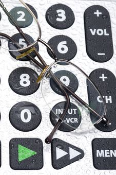 Remote Control And Glasses Stock Photos