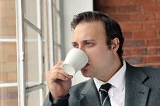 Suit Man Drinks Coffee And Thinks Royalty Free Stock Photos