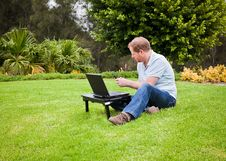 Free Man In Park Sending An SMS On His Cell Phone Royalty Free Stock Image - 17849926