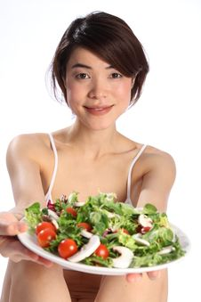 Japanese Girl Holds Out A Plate Of Green Salad Royalty Free Stock Image