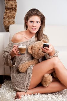 Free Girl Holding A Cup Of Coffee And A Remote Control Royalty Free Stock Photography - 17858067