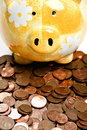 Free Yellow Ceramic Piggy Bank On A Pile Of Cents Stock Photo - 17871020