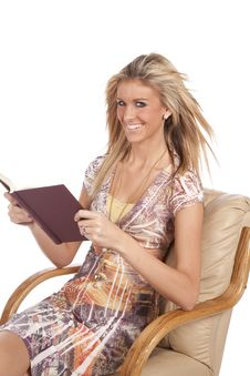 Woman In Chair With Book Looking Stock Photography