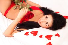 Girl Lying In Bed, Strewn With Hearts And Roses Stock Image
