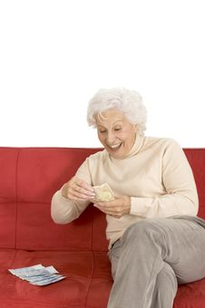 Elderly Woman On The Couch With Money In Hand Royalty Free Stock Photography