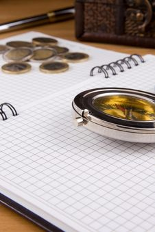 Compass, Pen And Coin On Notebook Royalty Free Stock Photos