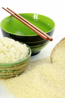 A Bowl Of Rice And A Pile Of Uncooked Rice Stock Photography
