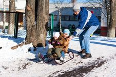 Free Father Pushing Children Down The Hill In A Sled Stock Photo - 17936050