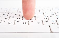 Human Finger On A Laptop Keyboard. Press A Key Stock Photo