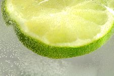 Slice Of Lime In Water With Bubbles Royalty Free Stock Images
