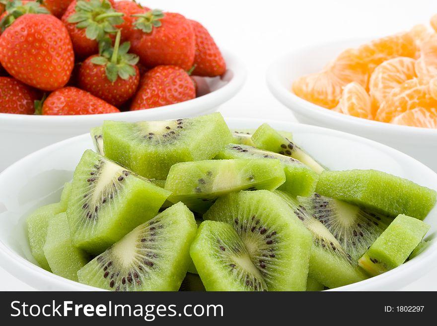 Kiwi, strawberry and mandarine, tangerine in white bowls