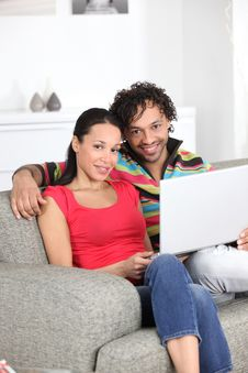 Free Smiling Couple On A Sofa With Laptop Stock Image - 18000751