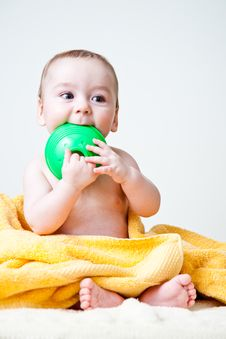 Free Baby Gnawing Green Toy On Yellow Towel Royalty Free Stock Photography - 18014477