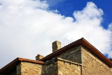 Old Stone House Against The Blue Sky With Clouds Royalty Free Stock Photo