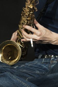 Close-up  Cross-legged Jazzman Plays A Saxophone Royalty Free Stock Photos