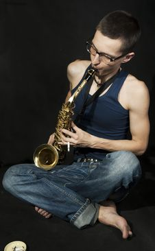 Cross-legged Jazzman Plays A Saxophone Stock Image