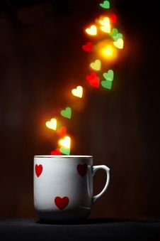 Free Cup With Steam Of Glowing Hearts On Dark Stock Image - 18043241