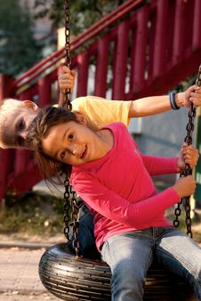 Boy And Girl On Swing Stock Image
