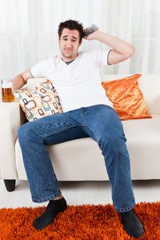 Young Boy With A Glass Of Beer And Remote Control Royalty Free Stock Image