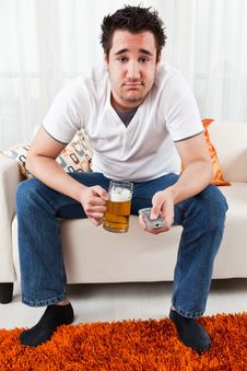 Young Boy With A Glass Of Beer And Remote Control Royalty Free Stock Photography