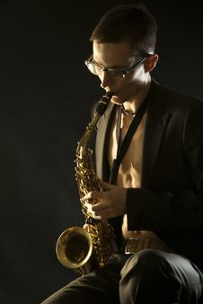 Young Jazzman Plaing A Saxophone On Black Royalty Free Stock Images