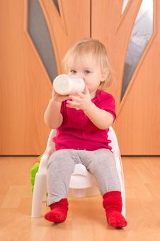 Adorable Baby Sit On Baby Chair And Drink Milk Royalty Free Stock Images