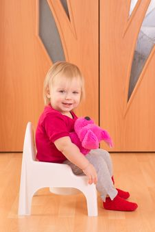 Adorable Baby Sit On Toilet Chair With Toy Dog Stock Photos