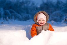 Free Adorable Baby Sit And Digging Hideout Hole In Snow Stock Image - 18100711