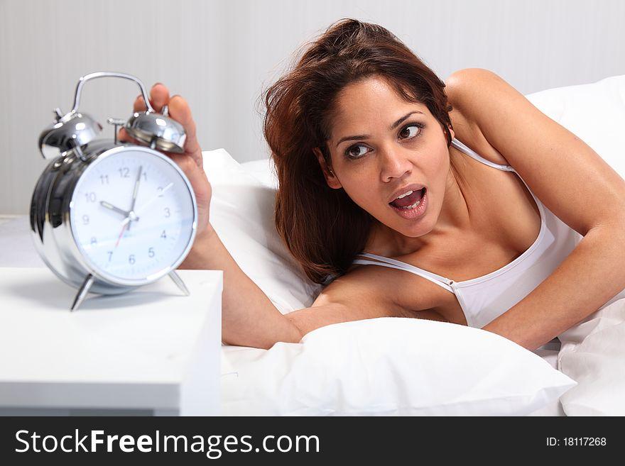 Beautiful woman waking up reaching for alarm clock