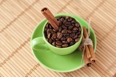 Free Coffee Beans And Cinnamon Stick In A Green Cup Stock Photos - 18181913