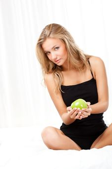 Free Beautiful Woman Sitting On Bed And Holding Apple Royalty Free Stock Photography - 18196147