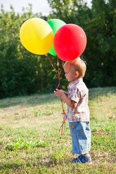 Free A Boy Is Standing On A Lawn With Colorful Balloons Stock Photography - 18215442