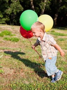 Free A Boy Is Standing On A Lawn With Colorful Balloons Stock Photo - 18215450