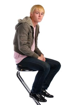 Young Man In Jacket With Fur Sits On Stool Royalty Free Stock Photography