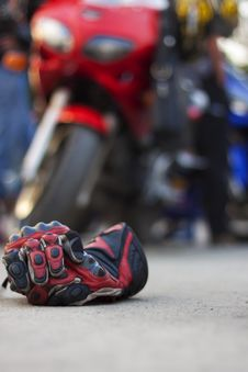 Free Motorcycle Gloves Against A Motorcycle Royalty Free Stock Image - 18249336