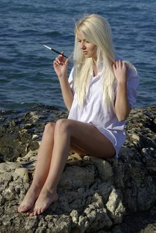 Free Speaking Blonde With A Cigarette Near Sea Stock Photos - 18261363