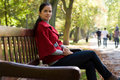 Free Woman Sitting In A Park On A Wooden Bench, Stock Photography - 18276262